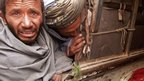 Mourner cries over bodies of Afghan civilians loaded into back of truck in Alkozai village
