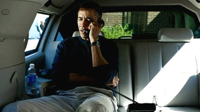 US President Obama on phone while in back seat of car
