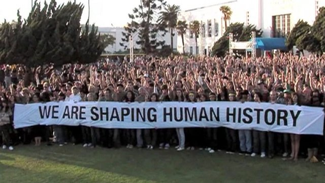 Crowd holding banner saying &quot;We are shaping human history&quot;