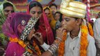 Newly engaged youth offer sweets to each other in the village of Vadia, Gujarat state, India - 11 March 2012