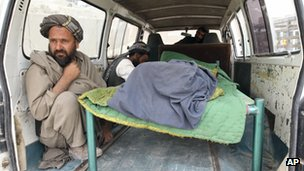 An Afghan man sits in the back of a bus with the body of a person who was allegedly killed by a US service member in Panjwai, Kandahar province south of Kabul, Afghanistan,