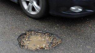 Car beside pothole