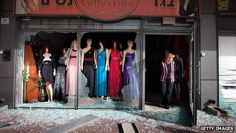 An Israeli woman surveys the damage to her shop following a rocket attack from the nearby Gaza Strip, on 12 March 2012 in Ashdod, Israel