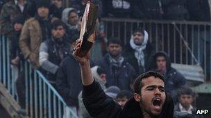 Man brandishing half burned Koran
