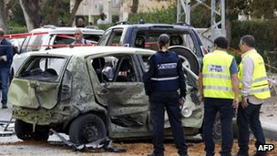 Israeli police inspect cars that were damaged after a Palestinian rocket attack in Ashdod. Photo: 12 March 2012