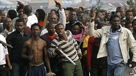 A crowd, armed with clubs, machetes and axes on a rampage on May 20, 2008 during xenophobic clashes at Reiger Park, south of Johannesburg