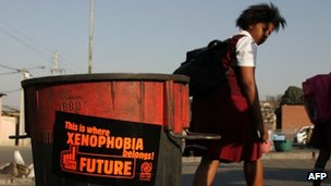 A picture taken on August 12, 2009 shows South African school girls walking past a trash bin bearing an a sticker against xenophobia in Alexandra township, north of Johannesburg
