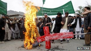 Protesters burn an effigy of US President Barack Obama and a red cross in Jalalabad province, Afghanistan