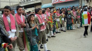 Syrians Kurds perform a traditional dance in Qamishli during a protest on 12 March 2012