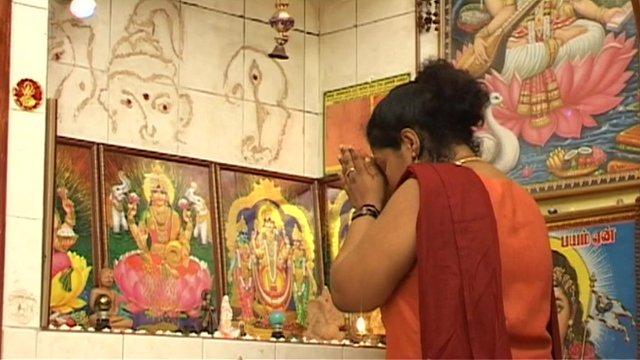 Woman prays before framed Hindu deities.