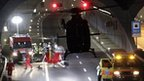 A helicopter takes off from the entrance of a tunnel into which the bus crashed in Sierre