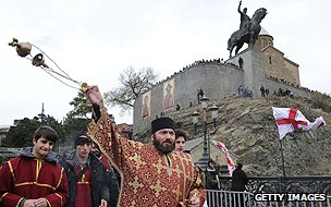 A priest leads a procession in Tbilisi