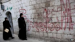 Women walk past graffiti saying &quot;Freedom&quot; in the Syrian city of Idlib (11 March 2012)