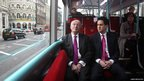 Labour leader Ed Miliband and London mayoral candidate Ken Livingstone sitting on a bus