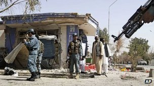 Afghan policemen are seen at the scene of a bomb explosion in Kandahar south of Kabul, Afghanistan, Wednesday, March 14, 2012.