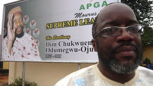 Emeka Ojukwu Jr in front of a poster showing his late father