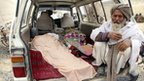 An elderly Afghan sits next to the covered body of a person allegedly killed by a US soldier in Kandahar province, 11 March.