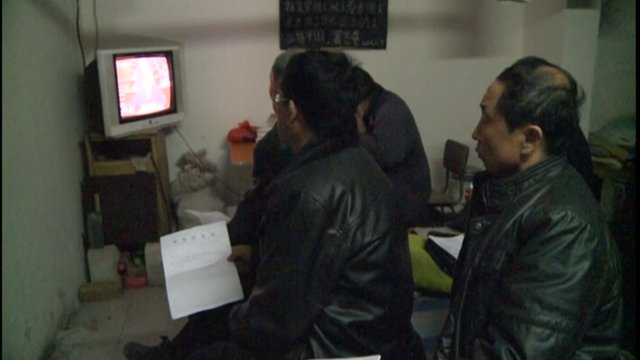 Chinese man and woman watch television set