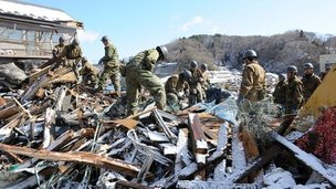 Military personnel search for survivors