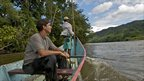 Erik Patel heading upriver in Marojejy National Park on a boat (c) Tuppence Stone