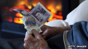 A old person holding money in front of a gas fire