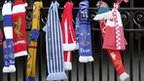 The scarves of several football clubs are seen on the gates during a service at Anfield football stadium in Liverpool, north west England on April 15, 2008
