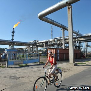 A woman rides her bike near the Mozyr oil refinery, Belarus