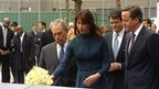 Samantha Cameron places flowers on the Ground Zero Memorial, watched by David Cameron