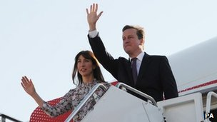 David Cameron waves as he boards a plane to New York 15 March 2012