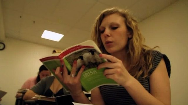 "Student in classroom refers to book entitled ""Irish""."