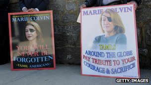 People standing with placards bearing the image of Marie Colvin after her funeral on March 12, 2012