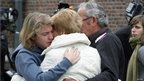 People console each other outside the school in Lommel
