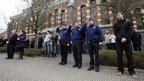 Police officers salute as neighbours and relatives of victims of a bus crash in Switzerland observe a minute of silence in front of 't Stekske school in Lommel