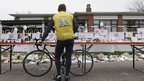 A man holds his bike as he stands for one minute of silence in Lommel