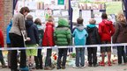 Children look at pictures outside St Lambertus primary school in Heverlee