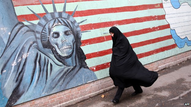An Iranian woman walks past an anti-US mural painted on a wall