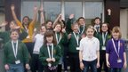 The Glaitness School Report team throw their hands in the air and smile for the camera