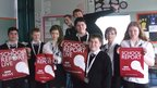 The team at Cumbernauld High School hold up their School Report posters as they pose in a classroom