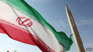 An Iranian flag blows in the wind next to a missile