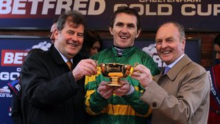 "Jockey AP McCoy celebrates with owner JP McManus and trainer Jonjo O""Neill (right)"