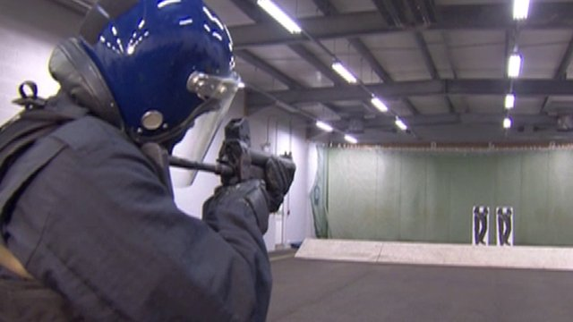 An officer firing plastic bullets