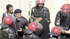 Riot police and Coptic priests stand outside Cairo cathedral - 18 March