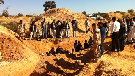 People gather at an excavated mass grave