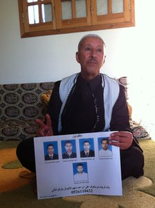 Abu Salam holding a poster with pictures of his sons