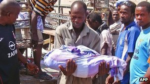 A Somalian carries the dead body of a child killed with four family members by a mortar shell that struck their home in Wardhigley district, Mogadishu on March 19, 2012.
