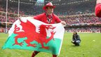 Centre Jamie Roberts proudly flies the Welsh dragon as he celebrates his second Grand Slam