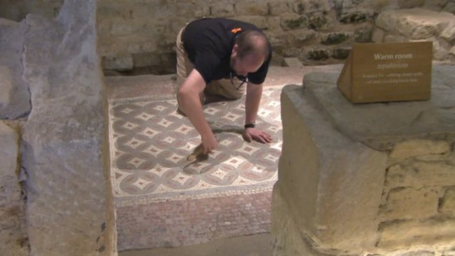 Dust is swept off a Roman mosaic at Chedworth Roman Villa in Gloucestershire