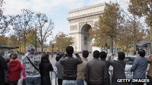 Chinese tourists taking photos of the Arc de Triomphe in Paris