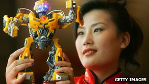 A model in Shanghai holds up a model of Bumble Bee a character from the US movie Transformers.