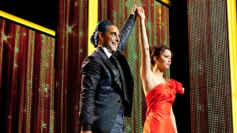 Caesar Flickerman (Stanley Tucci) and Katniss Everdeen (Jennifer Lawrence) in The Hunger Games. Photo credit: Murray Close